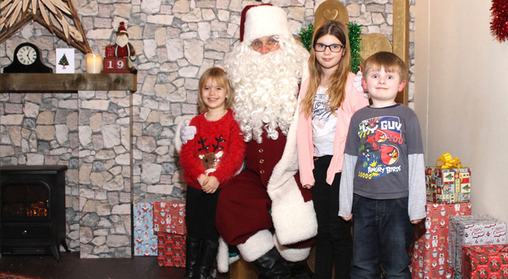 Children posing with Santa for Santa's grotto photography
