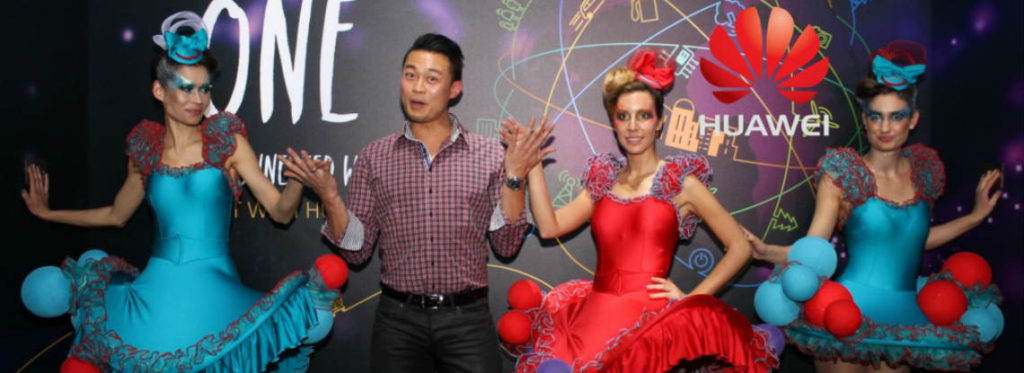 Man posing with exhibition performers at marketing event