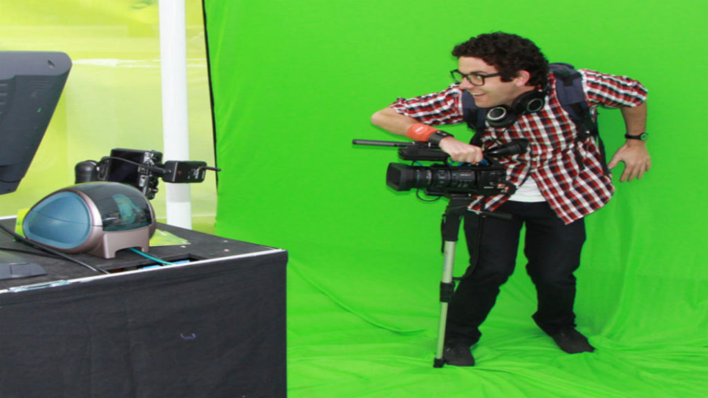 Man in front of a green screen with camera