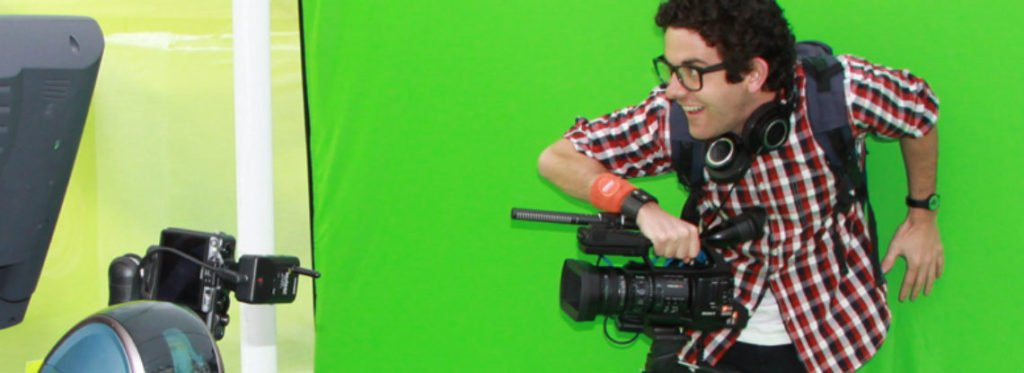 Man posing with camera against green screen