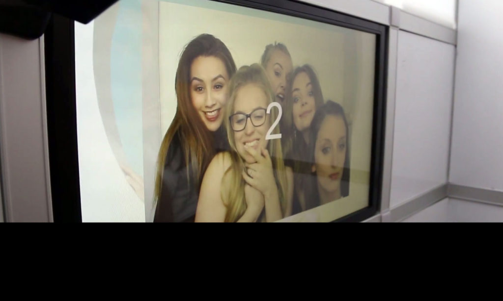 group of girls posing on night club photo booth screen with count down