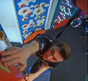 Man reaching to hit timer on climbing wall captured by climbing wall action video system