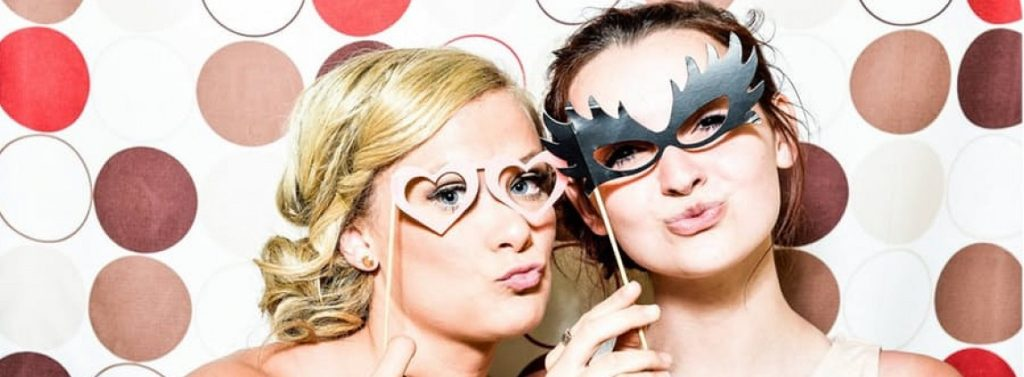 Two women posing with props in a photo booth