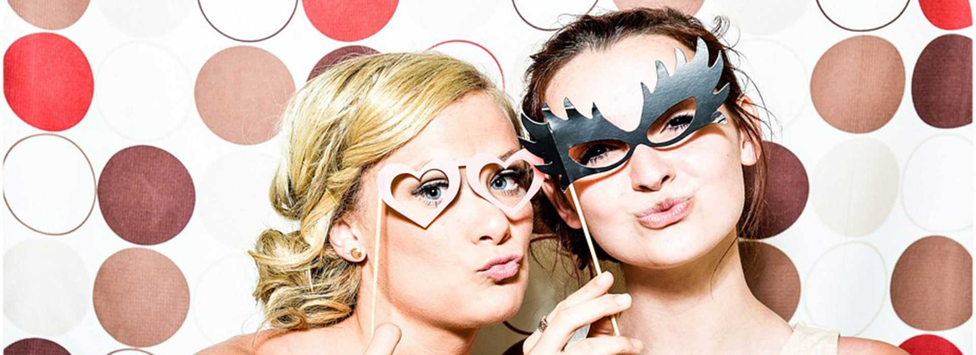 two girls posing with props in photo booth